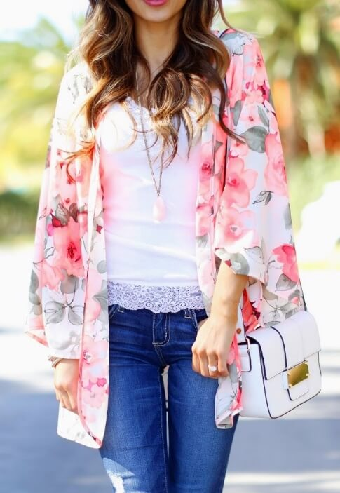 Trendy woman is wearing blue jeans and a pink floral kimono. Recycle last summer's floral kimono and wear it as a stylish spring cover-up.