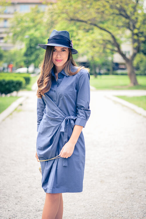 A woman walking in the park dressed in a solid blue dress with a wrap-over silhouette