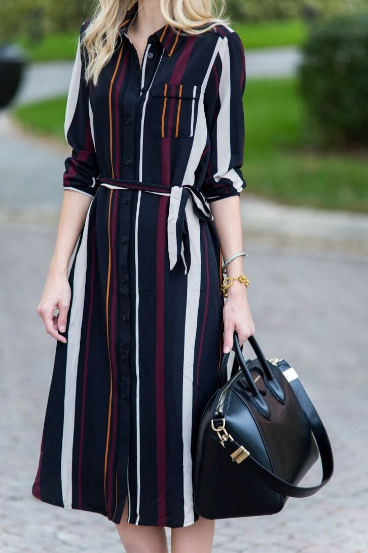 Working woman wearing a striped midi dress in three colors accent with a belt on the waist