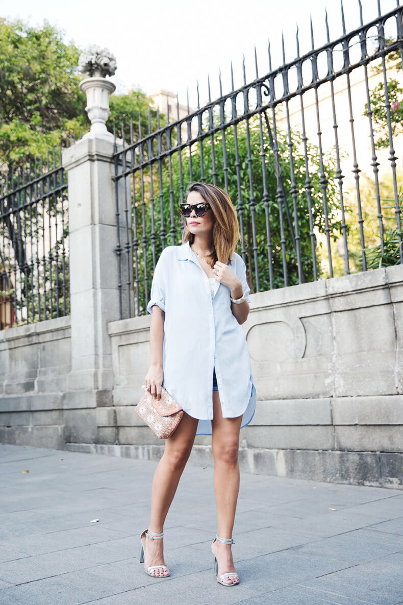 Woman dressed in boyfriend fit shirt dress over a white top and denim shorts.