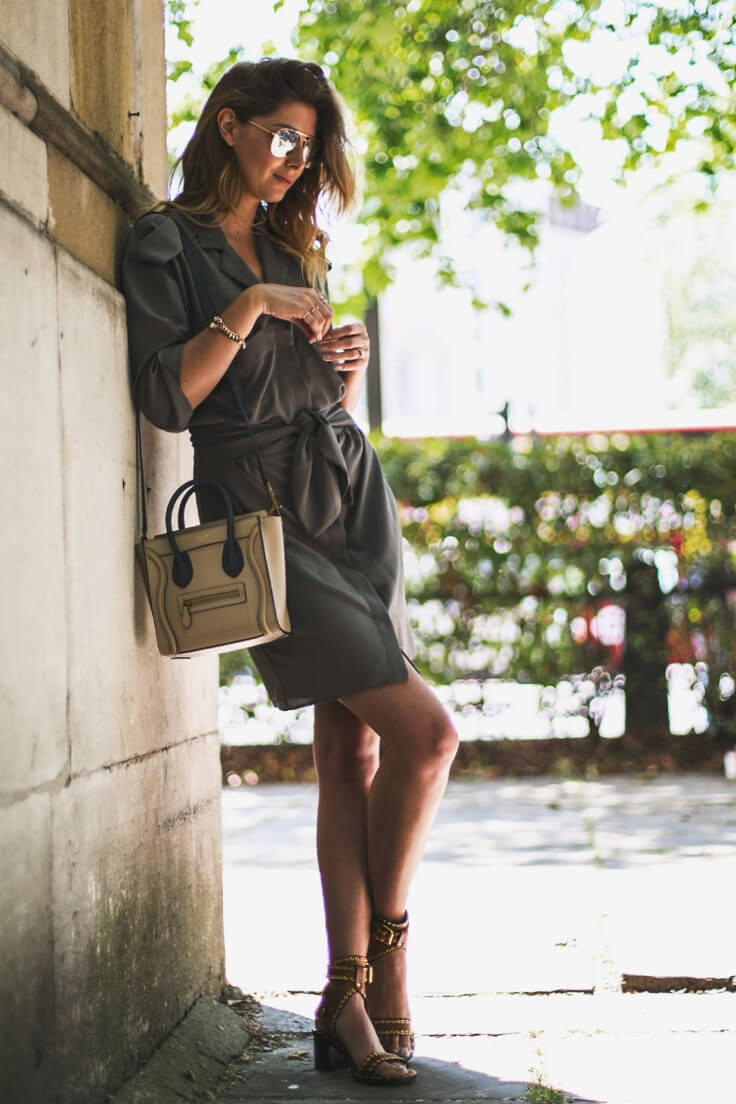Woman dressed in dark gray shirtdress finished with sandals with studs.