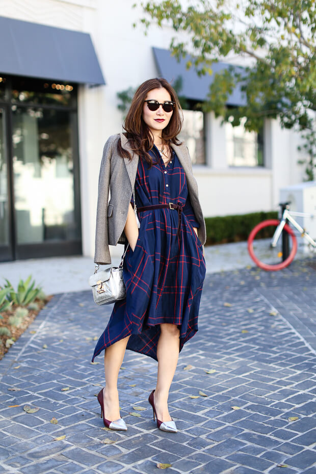 Smiling woman dressed in plaid shirt dress with asymmetric design accent with a belt on the waist.