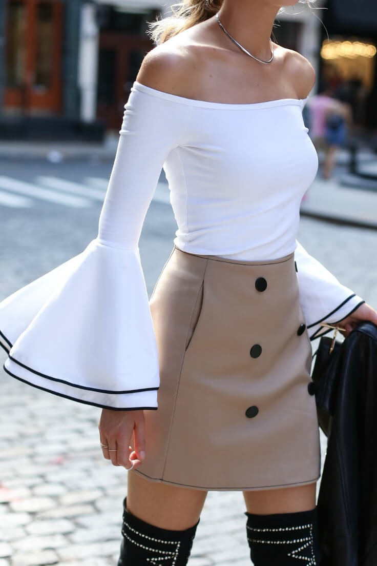 Elegant blonde is wearing an off-the-shoulder bell sleeve top and a high-waisted beige skirt. Create a classic silhouette with a slim-fitting bell sleeve blouse and a buttoned high-waisted skirt.