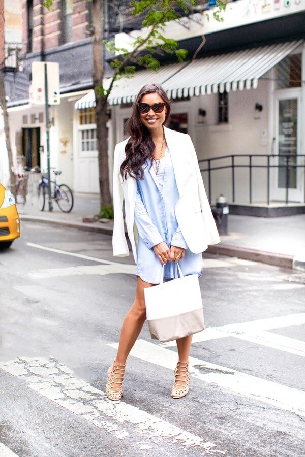 Happy woman in blue shirt dress combined with a white blazer, bag in white and beige and nude sandals.