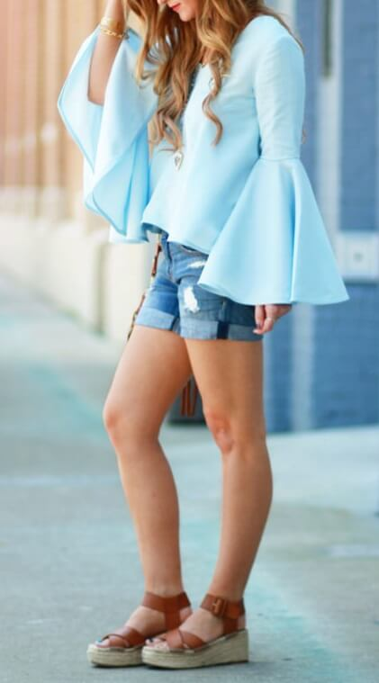 Fashionable woman is wearing cuffed denim shorts and a turquoise bell sleeve top. Infuse some spring color into your outfit with shades of turquoise blue and distressed denim.