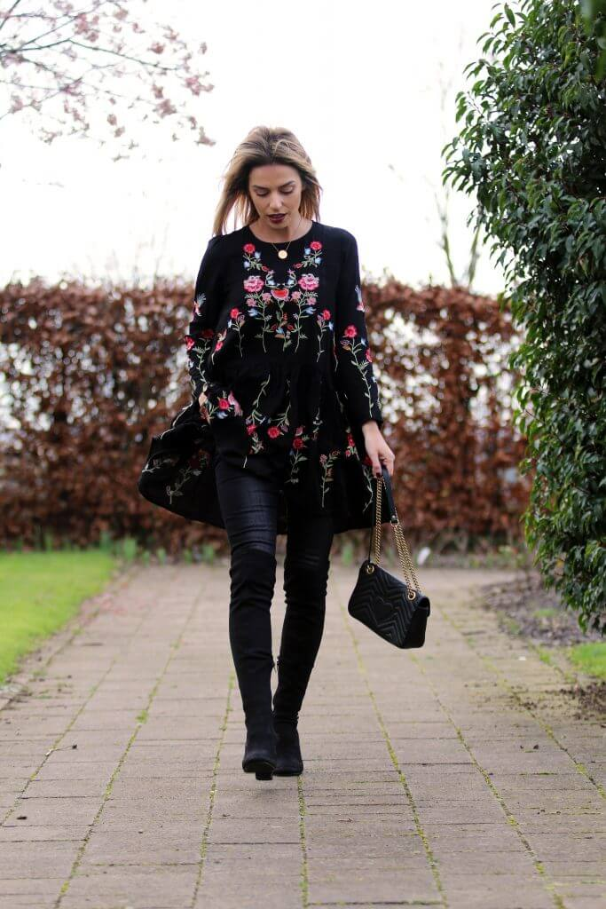 Trendy woman is wearing a black embroidered floral dress and black suede boots. When it's still cold out, nothing is cooler than an embroidered floral dress and thigh-high suede boots.