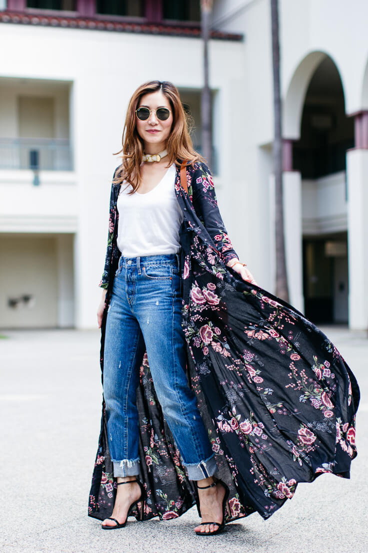 Woman with ribbed boyfriend jeans, white top and flower pattern shirt dress worn like a long cardigan for an effortlessly chic look.