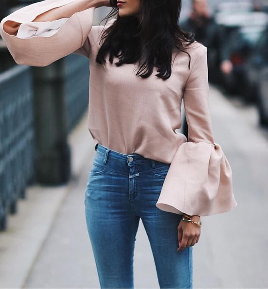 Chic brunette in high-waisted jeans and a pink bell sleeve top. You don't need much to style a silk bell sleeve top – just add blue jeans and you're good to go.