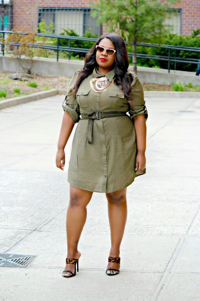 The military green dress is accented with a belt on the waist and statement-making necklace