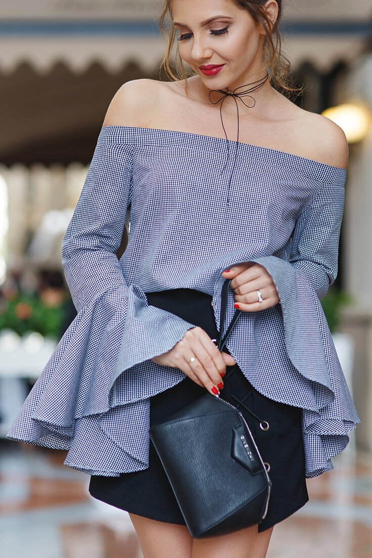 Stylish woman in an off-the-shoulder top with bell sleeves and a lace-up mini skirt. If it's drama you want, look no further than this gray bell sleeve blouse and black lace-up mini skirt.