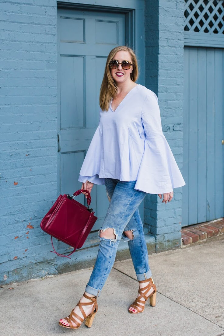 Fashionable woman in ripped blue jeans and a blue bell sleeve top. Combine edgy and stylish with the sweet mix of bell sleeves and denim.