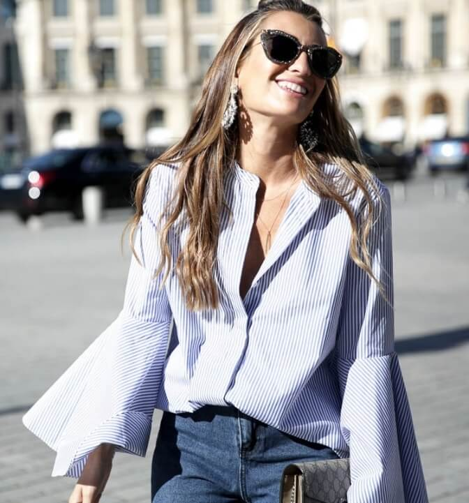 Chic blonde woman wearing a button-down bell sleeve blouse and blue jeans. Keep things classic and elegant by pairing your button-down bell sleeve blouse with basic blue jeans.