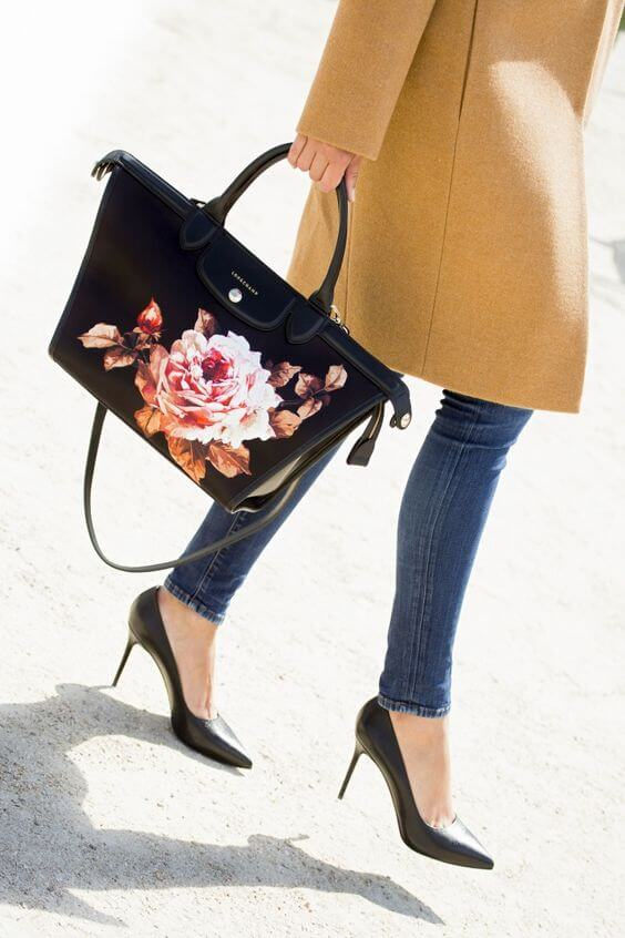 Elegant woman is wearing a long camel coat and a floral handbag. What's classier than a camel-colored coat and stiletto pumps? A slinky floral handbag, of course.