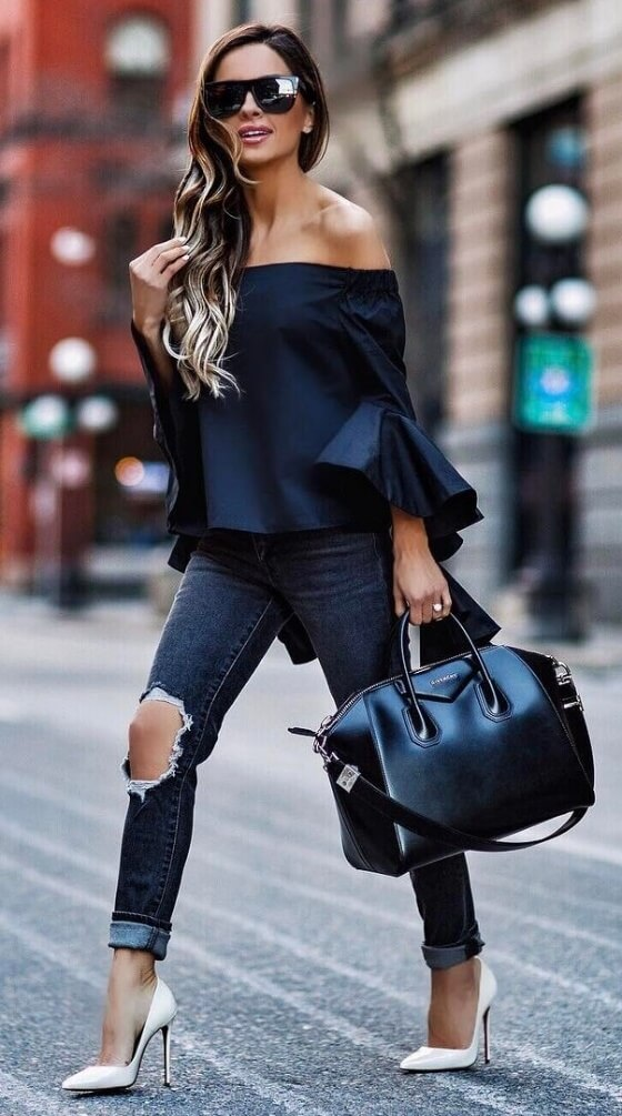 Edgy woman is wearing ripped skinny jeans and a black off-the-shoulder bell sleeve blouse. Ripped denim was made for a bit of drama, and this bell sleeve blouse is a real showstopper.