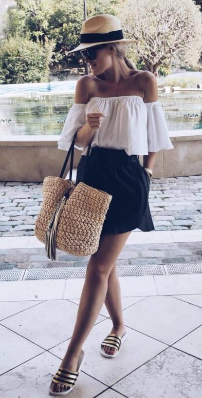 Casual blonde woman is wearing a black skirt and a white off-the-shoulder bell sleeve blouse. Be classy and right on trend in this off-the-shoulder bell-sleeve style paired with an effortless black skirt.