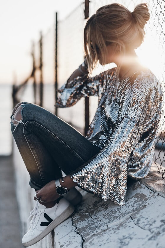 Trendy blonde woman is wearing ripped denim jeans and a sequined bell sleeve top. Sequins and bell sleeves make an unusual style combination that simply works.
