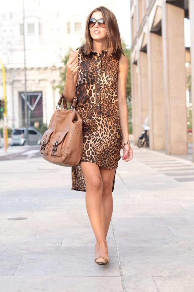 Girl walking in the city dressed in an asymmetric dress with leopard pattern