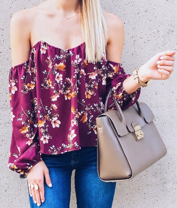 Trendy woman is wearing skinny blue jeans and a floral off-the-shoulder top. What could be sexier than bare shoulders adorned in bright florals?