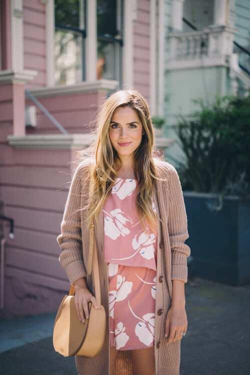 Stylish woman is wearing a floral romper and an oversized woolen cardigan. It doesn't get any sweeter than a cute floral romper and a luxurious long woolen cardigan.