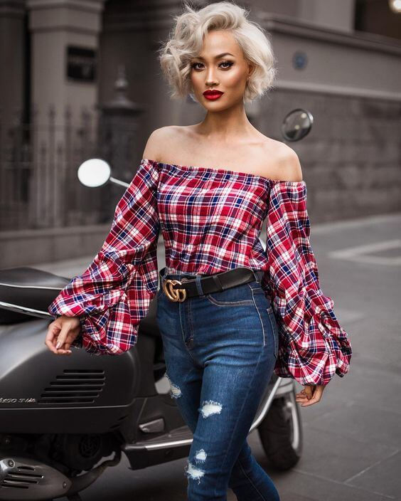 Chic blonde woman wearing high-waisted blue skinny jeans and an off-the-shoulder plaid blouse with bell sleeves. Every day is a catwalk day in this ensemble of blue denim and plaid bell sleeves.