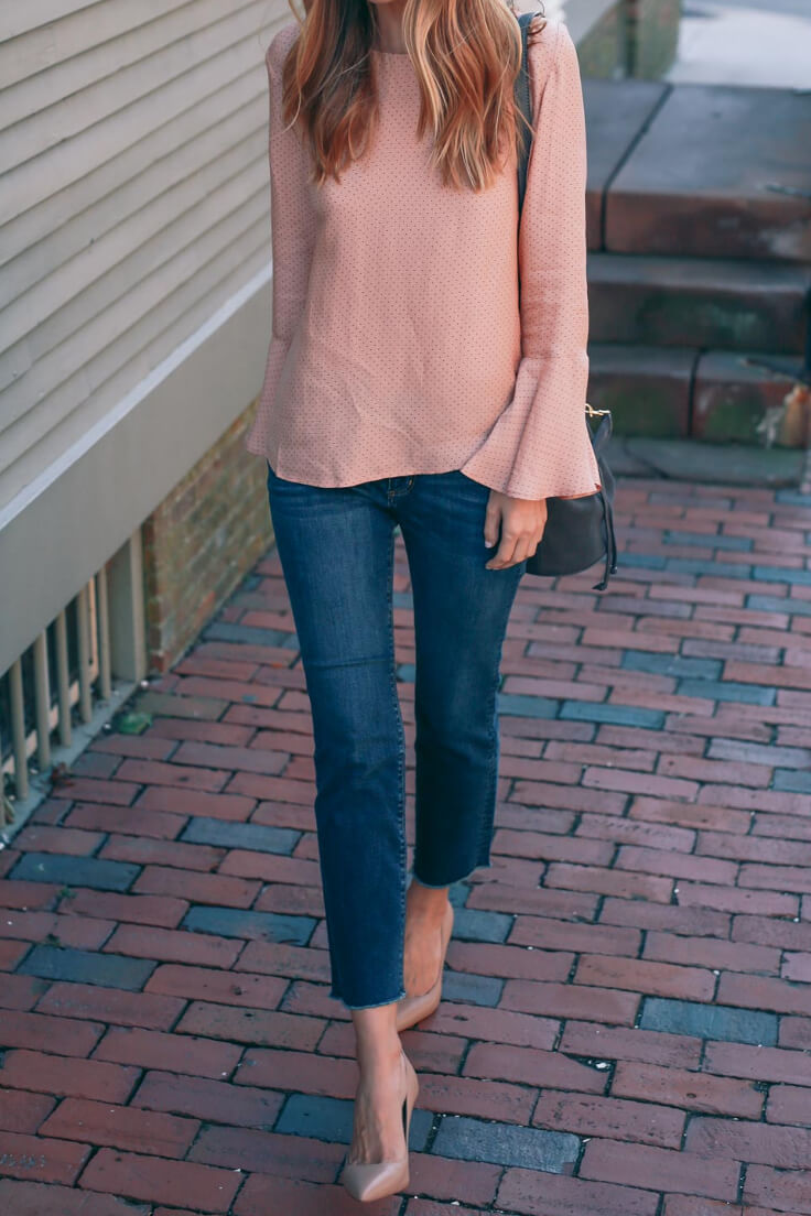 Chic woman is wearing dark blue denim jeans and a blush pink bell sleeve blouse. If you're cautious about trying new trends, this blush pink top is a subtle way to ease into the bell sleeve shape.