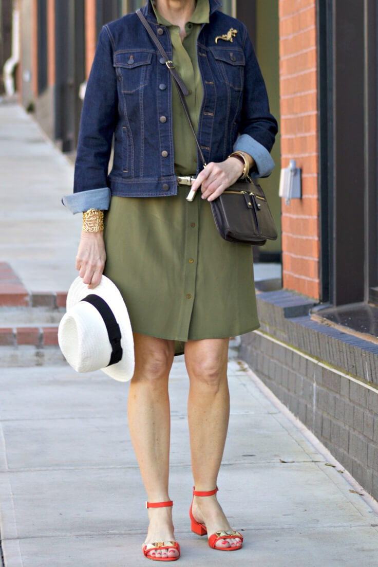 Woman wearing military green shirtdress and dark blue denim jacket