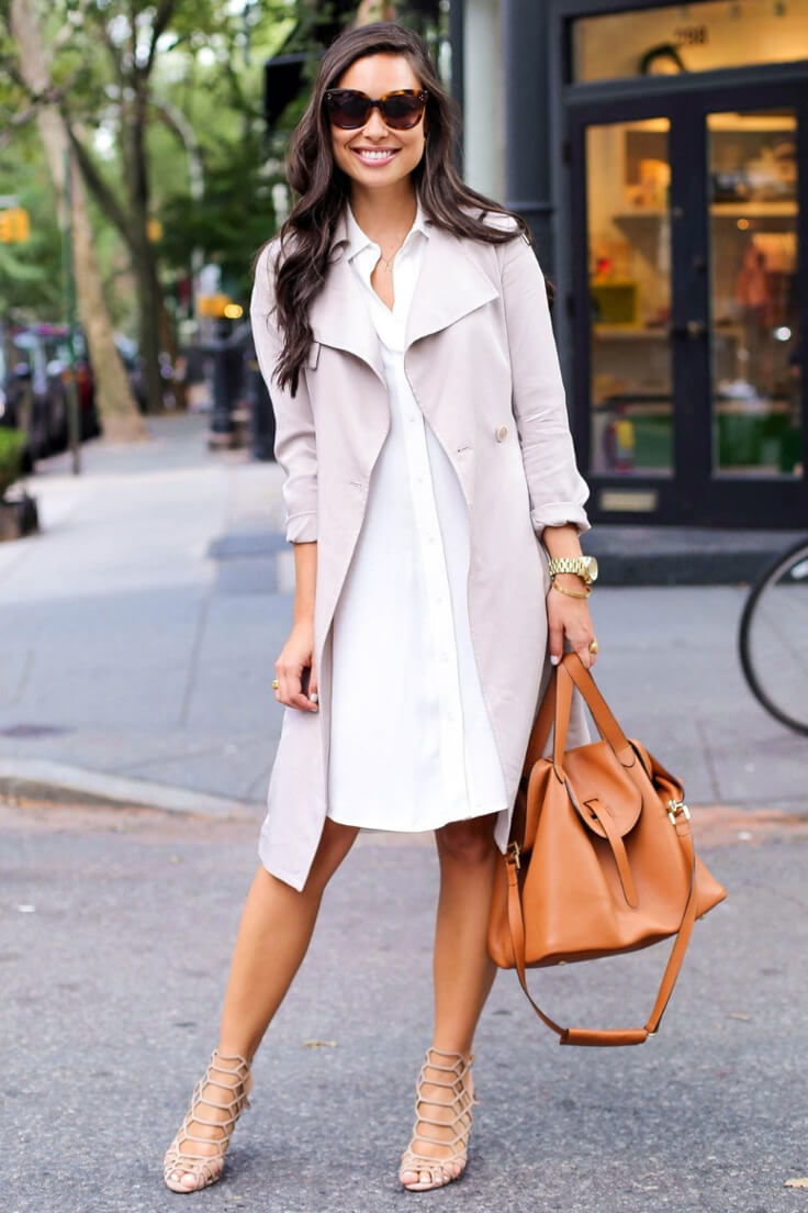 Smiling young lady with a shirt dress, light trench and hobo leather bag in the cognac color.