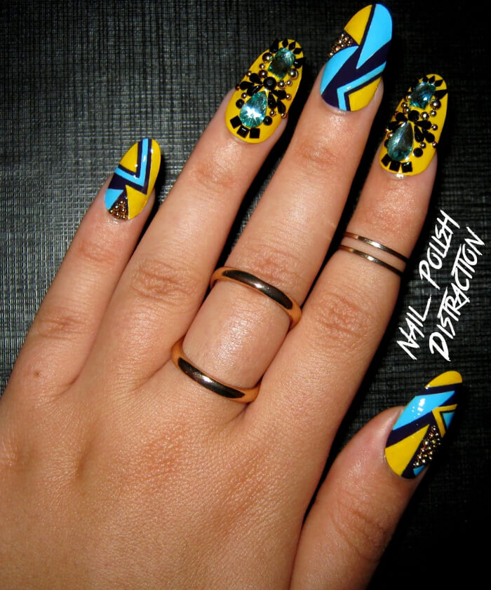 With this intricate nail design, each nail has its own unique look. Featuring triangles and other geometric shapes on some nails and gold studs and gems on others, this manicure is sure to please.