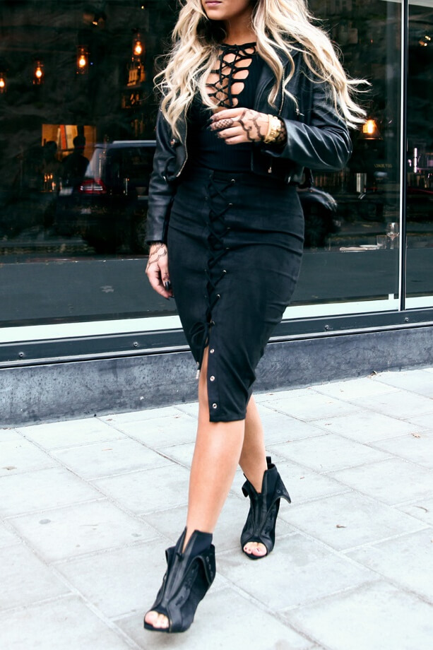 Walking in style: blonde in all black outfit with a clear accent on a lace-up top