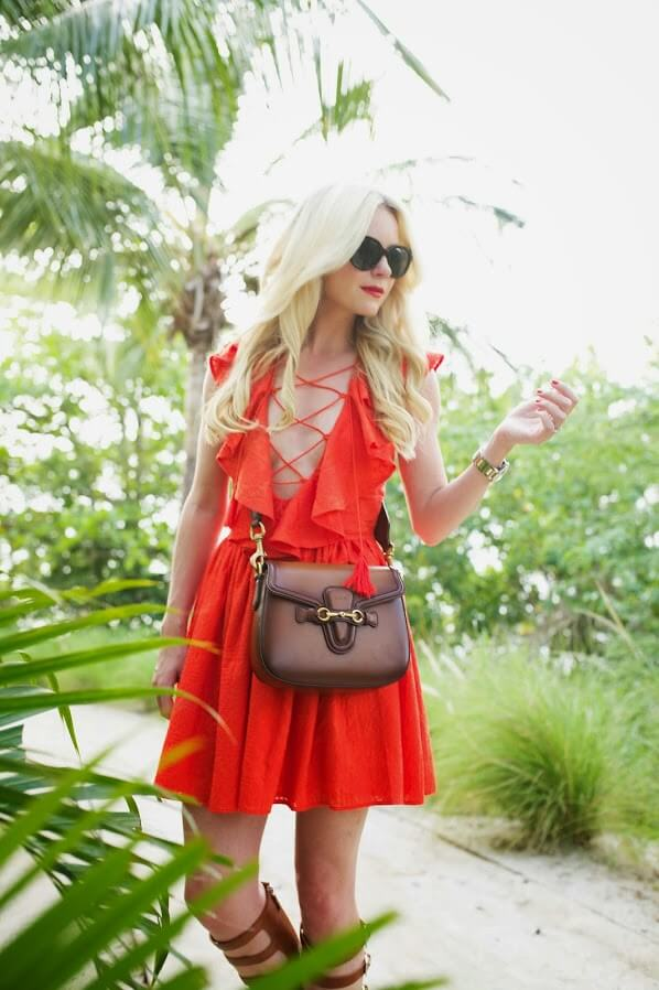 Blondie dressed in coral beach dress with laces and ruffles details on the neck. The lace up details in a bright color highlights your suntan and delicately shows the curves.