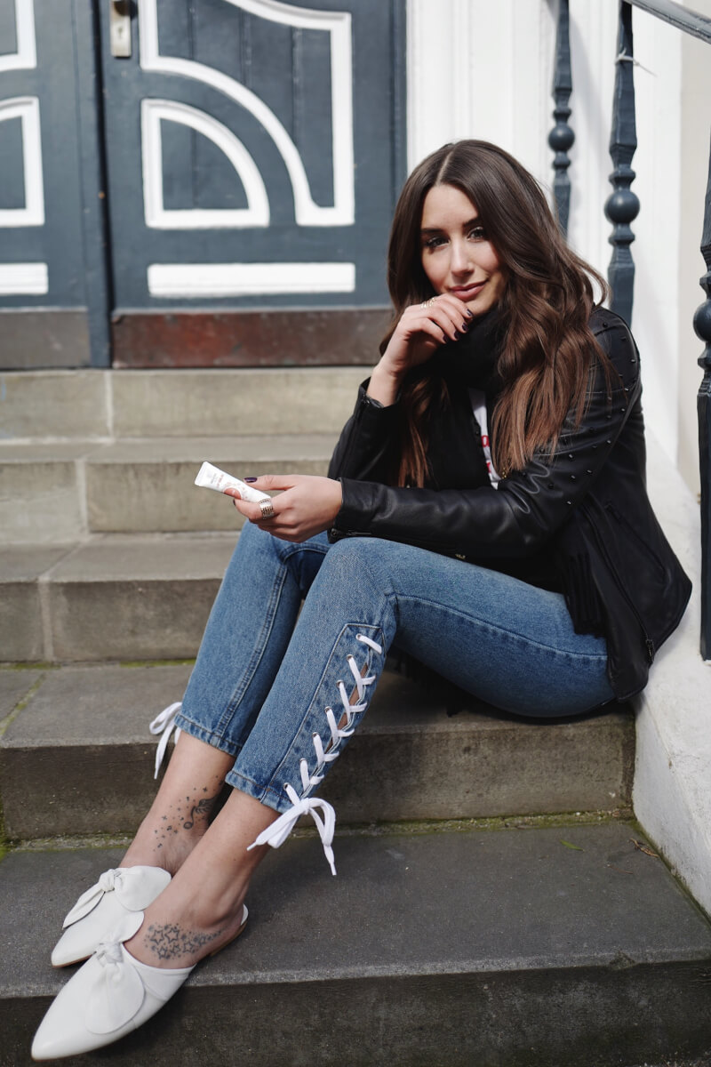 A young lady dressed in leather jacket and skinny denim with lace up details on the ankle. An excellent way to transform boring jeans into something chic.