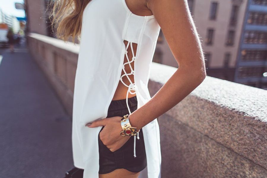 White asymmetric top with lace up details on the side combined with basic black shorts. This is an easy way to turn your old basic white top into trendy garment giving a sexy touch to every summer outfit.