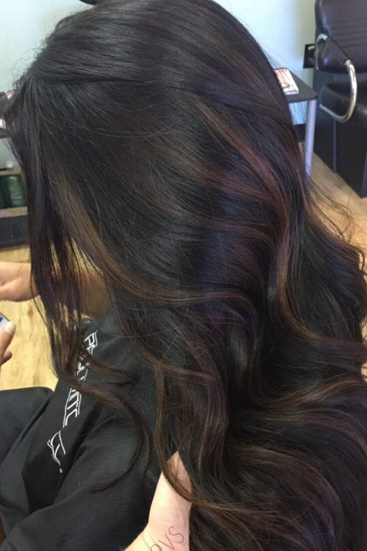 This model's wavy dark brown hair is ever so lightly highlighted with some subtle, light