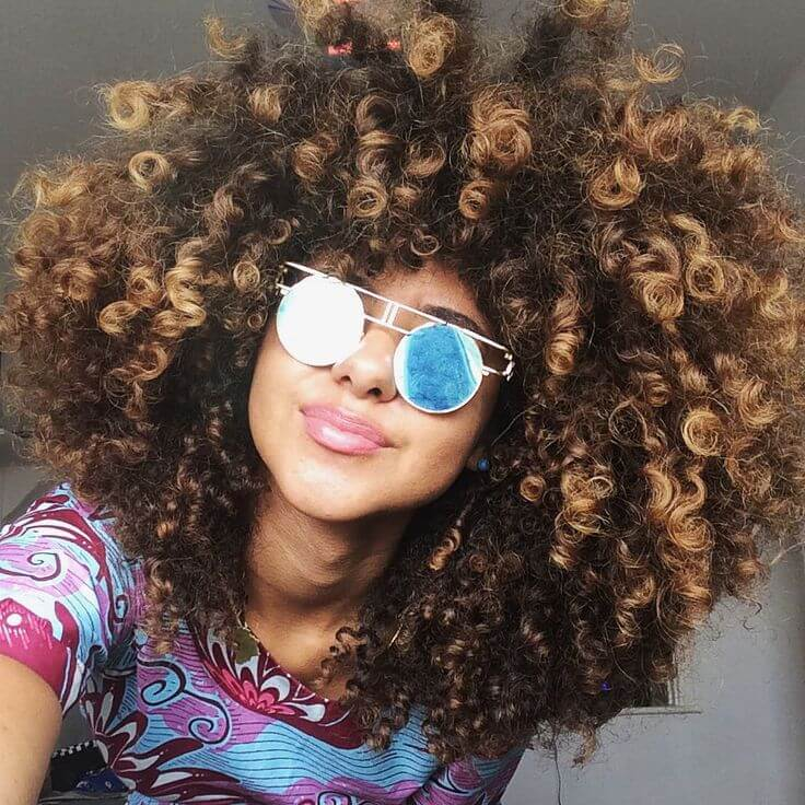 This gorgeous model is rocking all-over golden highlights in her naturally curly 'do.