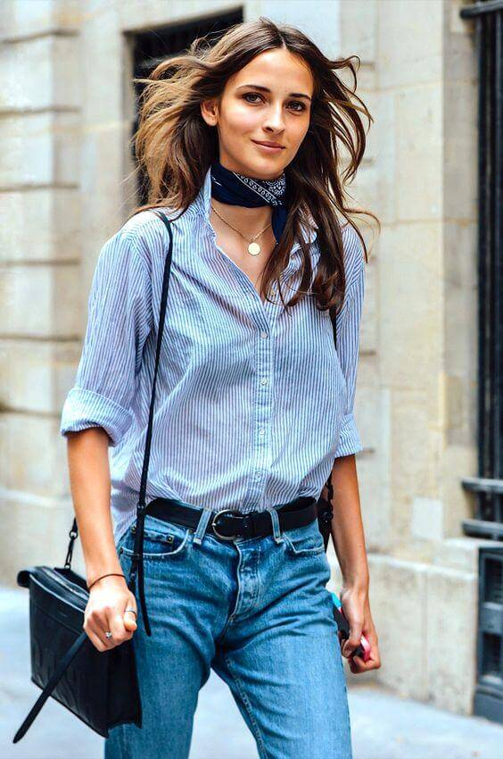 Another lesson in French style – choose menswear items but wear them in an ultra-feminine way. Here a button-down blouse and blue jeans get a dose of elegance with a neck scarf added to the all-blue ensemble.