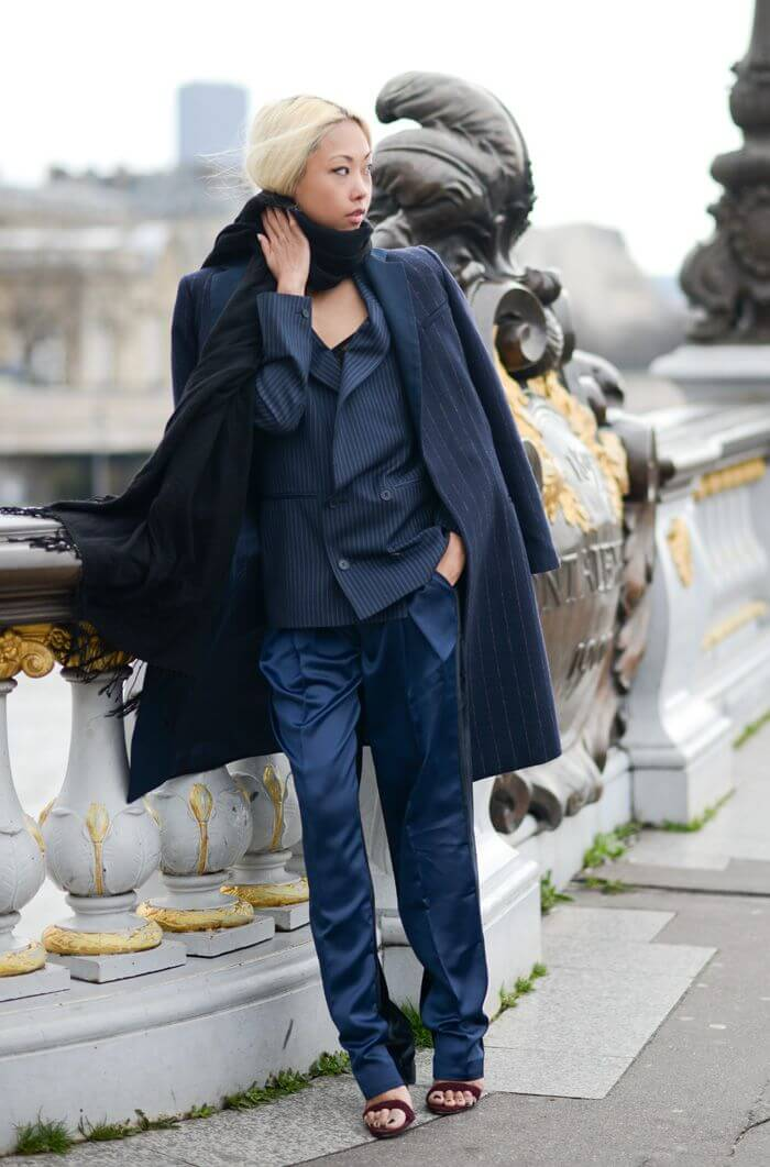 Vanessa Hong wearing pinstripe coat, black scarf, pinstripe double breasted blazer, silk trousers and sandals