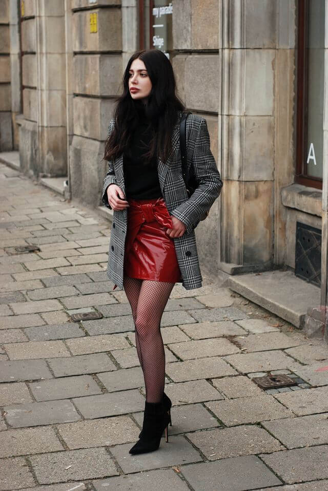 Stylish woman wearing cashmere turtleneck, blazer, red latex skirt, fishnets and ankle boots
