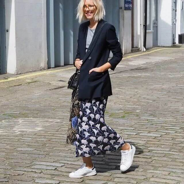 Alexandra Stedman putting together black blazer, floral printed skirt with Adidas Stan Smith trainers