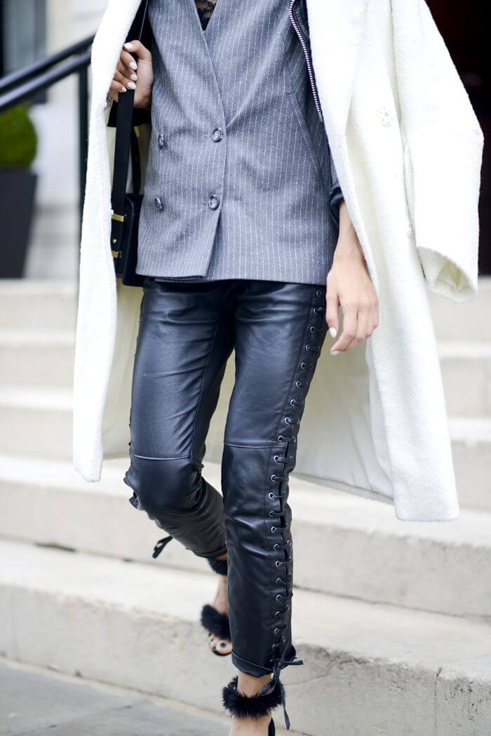 Fashion blogger clearly demonstrates the mix of pinstripe blazer, white coat, pour leather pants and faux fur sandals