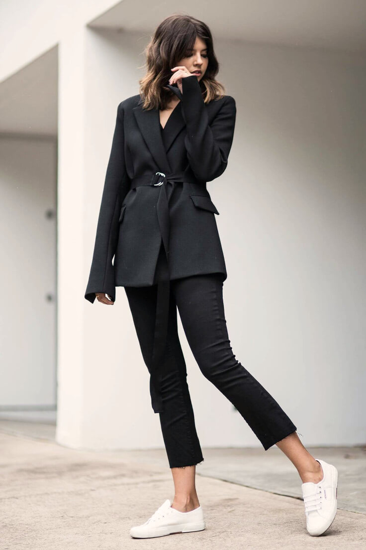Stylish woman wearing black blazer with d-ring belt, cropped bootcut black jeans and classic tennis white shoes