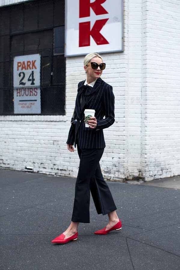 Super stylish woman wearing wide-leg flared trousers, striped double breasted blazer, sunglasses complementing with red lipstick and shoes.