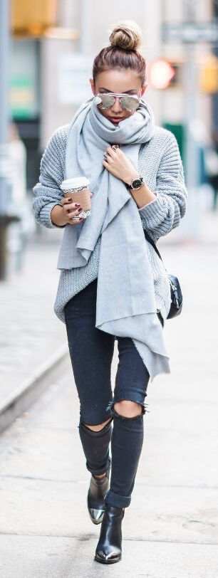 Here we have every street style star's everyday uniform: ripped black skinny jeans, black leather booties plus beautiful dove gray basics. Give it a full spin with an oversized gray sweater and matching oversized wrap around pashmina scarf.